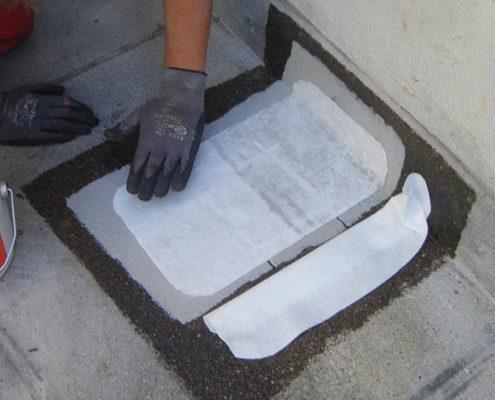 An Hand dieses Fotos kann man schön erkennen, wie auf einem bituminösen Flachdach eine Reparatur mit Kemperol und Fließeinlage durchgeführt wird. Hier ist zu beachten, dass die Fließeinlage beidseitig getränkt wird