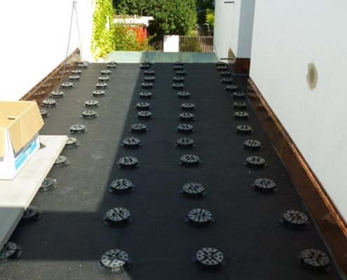 Ansicht einer Terrasse, die komplett neu erstellt wird und die Platten auf Stelz-Lagern verlegt werden